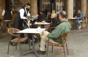 ep un camarero de nacionalidad extranjera atiende a varios clientes en una terraza